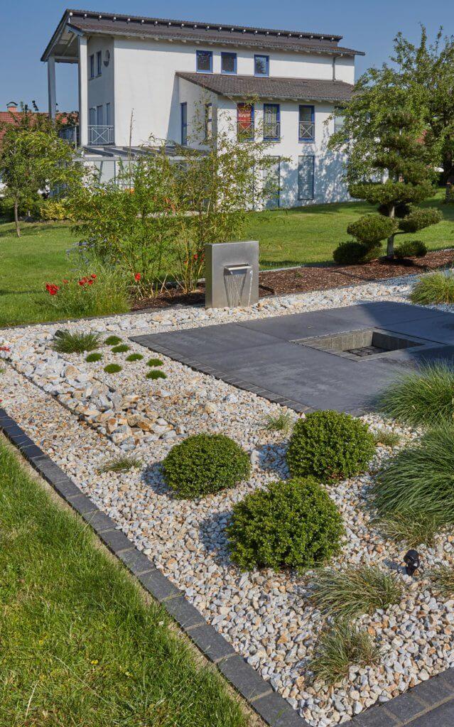 Koch Gartendesign baut auch Wasserinstallationen in die Gartengestaltung ein. Ein kleiner Wasserfall rundet die Garteninstallation mit Buchsbäumen und weißem Kies ab.
